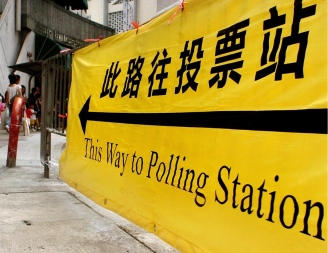 A woman walks pass an election information banner near a polling station in Hong Kong, 12 September 2004, as the territory's polls open for the 2004 Legislative Election. The polls opened 12 September 2004 at 7:30am local time (2330 GMT) across the former British colony in a legislative election seen as a gauge of sentiment towards the city's Chinese rulers and a reference on its democratic aspirations. AFP PHOTO/Philippe LOPEZ